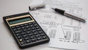 Calculadora preta em cima de papéis de contas e ao lado de uma caneta prateada e preta